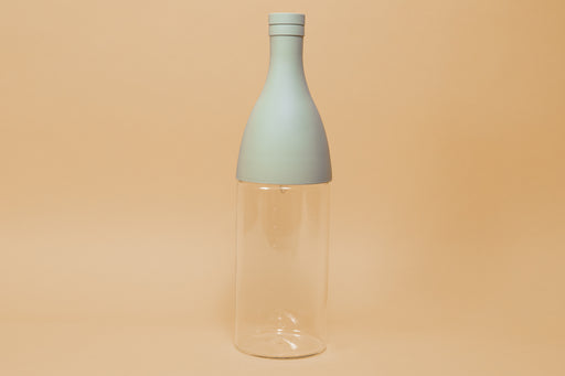 Glass bottle with powder green silicone champagne style upper half and cap