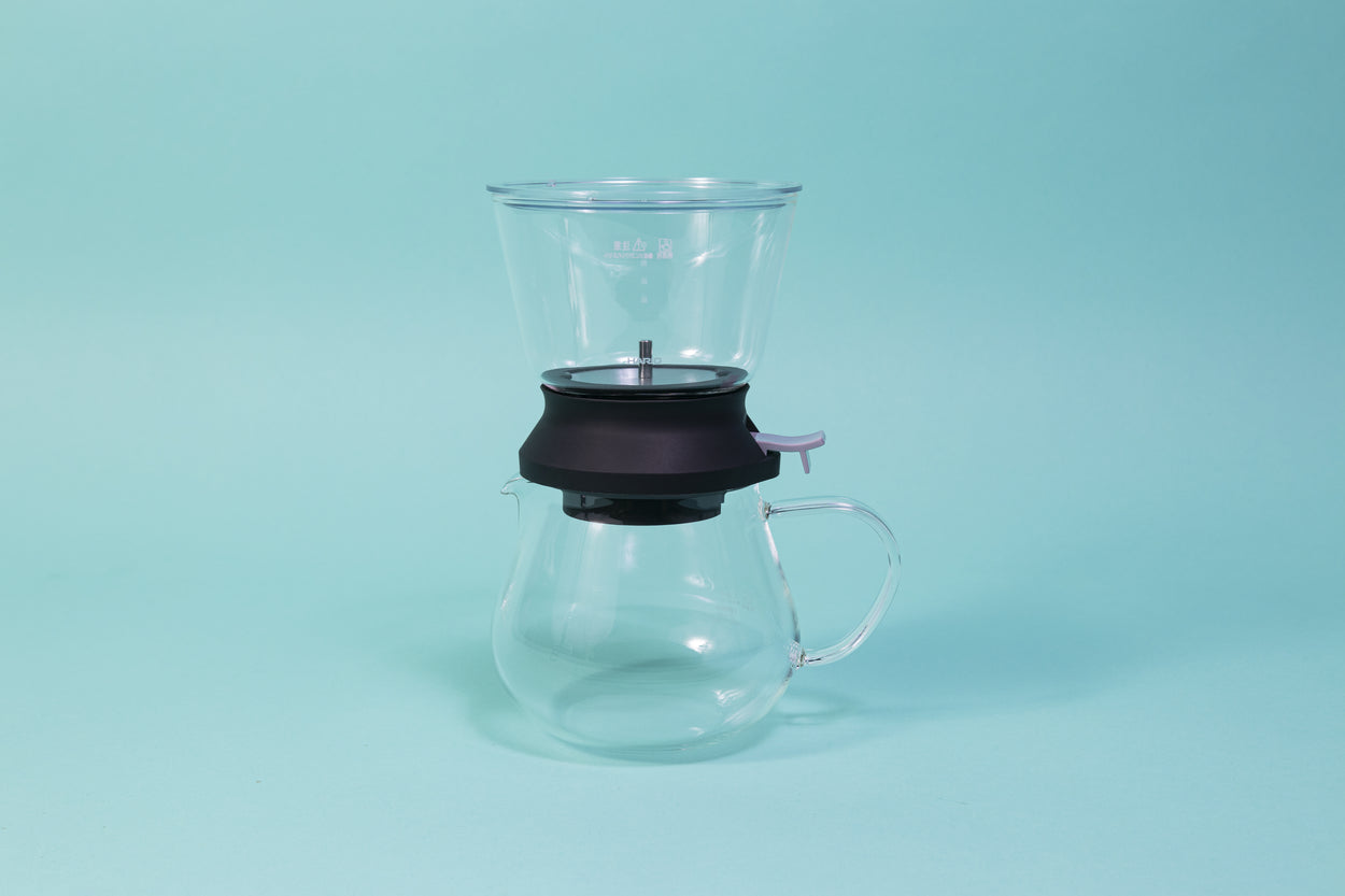 Cylindrical glass tea brewer and metal mesh strainer with clear plastic lid atop a black rubber base with plastic lever sitting on all glass bulbous server