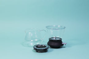 Cylindrical glass tea brewer and metal mesh strainer with clear plastic lid atop a black rubber base with plastic lever sitting next to all glass bulbous server and transparent black lid