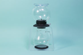 Globulous glass tear brewer and metal mesh filter with clear plastic lid atop a black rubber base with plastic lever switch on a clear acrylic stand above an all glass bulbous server with handle