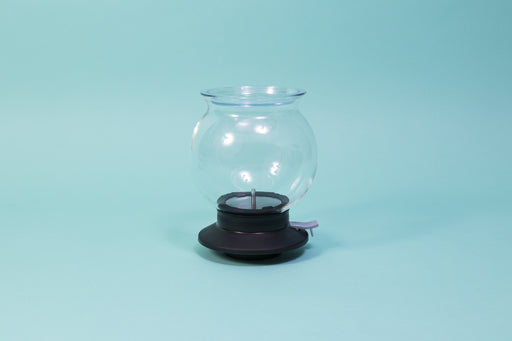 Globulous glass tear brewer and metal mesh filter with clear plastic lid atop a black rubber base with plastic lever switch