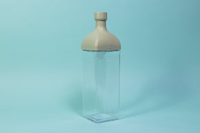 Clear plastic rectangular jug with green rectangular top and round cap.