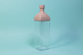 Clear plastic rectangular jug with pink rectangular top and round cap.