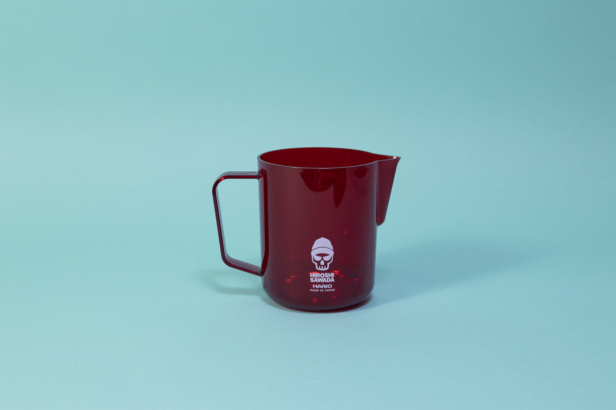 All plastic red milk pitcher with pour spout and handle. white skull decal