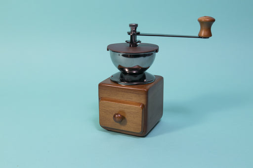 Wooden cube and drawer with dark metal grinder hopper and handle on top