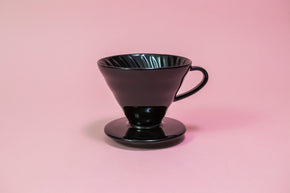 Black conical ceramic coffee dripper with handle and round base.