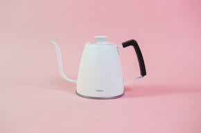 Matte white metal gooseneck kettle with white lid knob and black rubber handle cover.