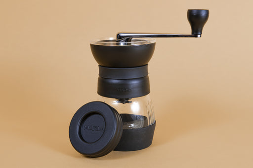 Black plastic coffee mill with handle attached to a glass container via screw top with a rubber base, and plastic lid.