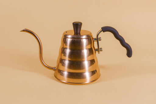 Copper goose neck kettle and matching lid with wood knob and brown rubber covered handle on an orange backdrop
