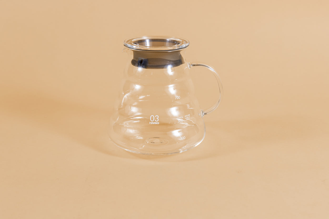 All glass beehive shaped coffee server with handle and glass lid with dark plastic rubber gasket on orange backdrop