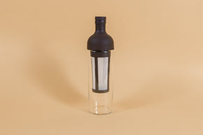 Tall glass container and white nylon mesh coffee filter, with brown rubber wine bottle shaped top on an orange backdrop