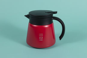 Red metal coffee server with black plastic handle and lid with pour spout on a teal backdrop.