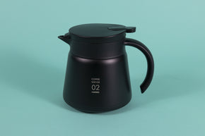 Black metal coffee server with black plastic handle and lid with pour spout on a teal backdrop.
