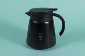 Tall black metal coffee server with black plastic handle and lid with pour spout on a teal backdrop.