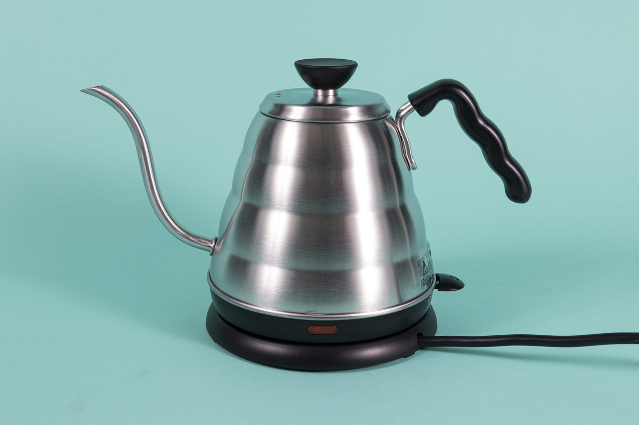 Stainless steel gooseneck kettle and matching lid with plastic base with red LED knob and black plastic covered handle on top a heating base with powercord on a teal backdrop