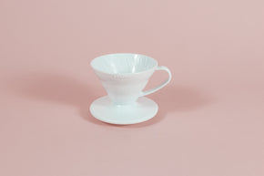 White all plastic cone shaped dripper with handle and round base on a pink backdrop