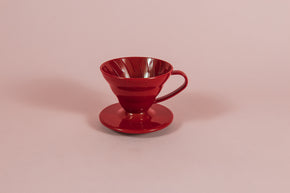 Red all plastic cone shaped dripper with handle and round base on a pink backdrop