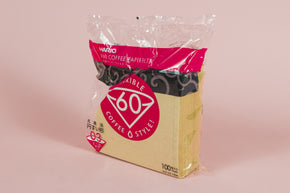 "Large pack of brown cone filters in plastic packaging with round pink with white text ""60"" graphic. on an orange backdrop"