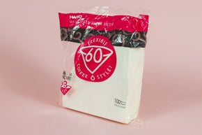 "Large pack of white cone filters in plastic packaging with round pink with white text ""60"" graphic. on an orange backdrop"