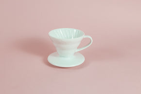 White cone shaped ceramic coffee dripper with handle and round base.