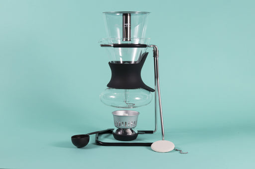 Glass carafe with glass syphon insert resting above an alcohol burner on a chrome stand with rubber sheathes surrounded by plastic scoop and cloth filter on a teal backdrop.