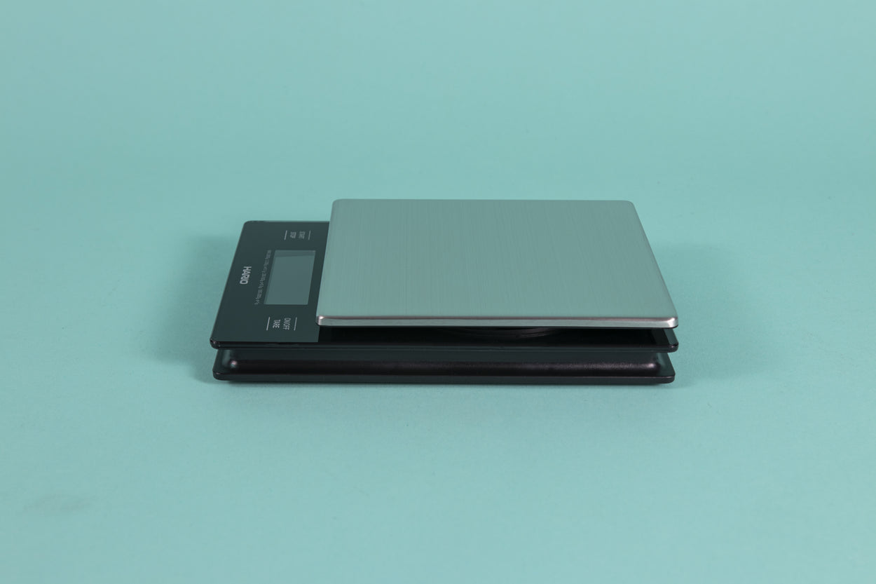 Black plastic scale with Digital LCD display and capacitive white text controls with a stainless steel weigh plate on a teal backdrop