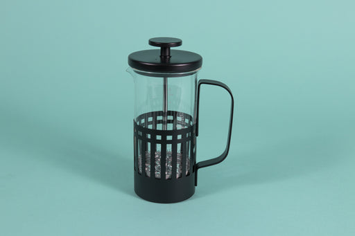 Slim glass server with metal mesh plunger for press coffee with black metal lid in an all black metal basket with handle on a teal backdrop