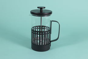 Glass server with metal mesh plunger for press coffee with black metal lid in an all black metal basket with handle on a teal backdrop