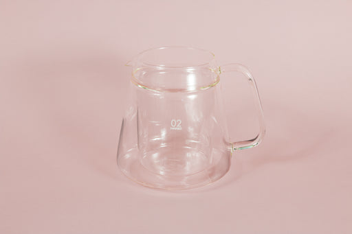 "Double walled all glass server with handle and white ""02"" text on a pink backdrop"