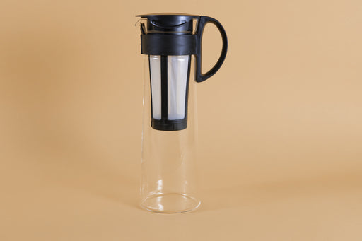 Tall glass server with white nylon mesh coffee filter insert and black plastic handle and lid
