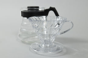 Clear plastic conical dripper with base and handle in front of a glass coffee server with black plastic handle and lid.
