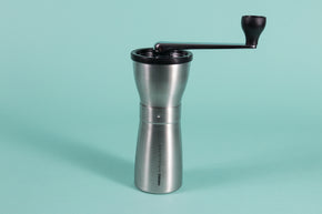 Slim silver metal coffee grinder with rubber lid and metal lever with black plastic knob at the end.