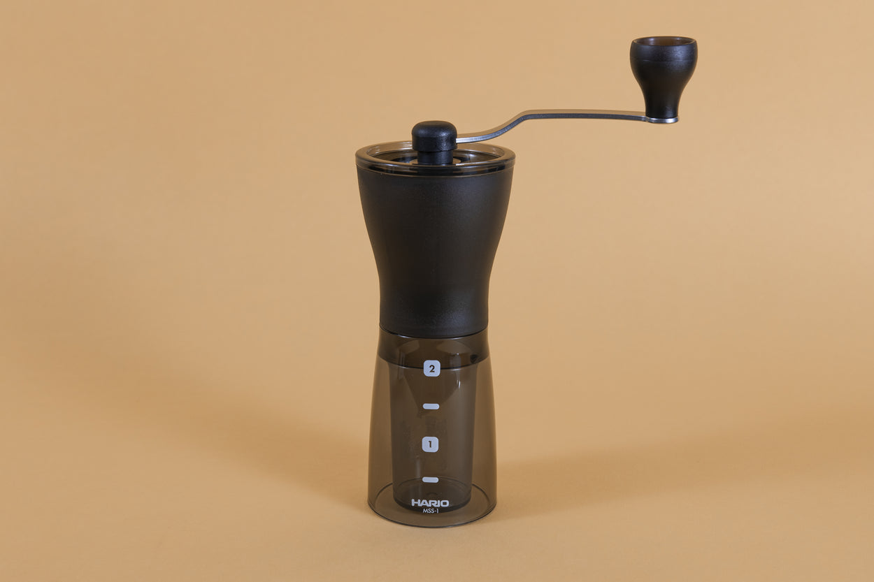 Slim black plastic Coffee Mill with handle atop a dark transparent plastic container with two level markings on an orange backdrop