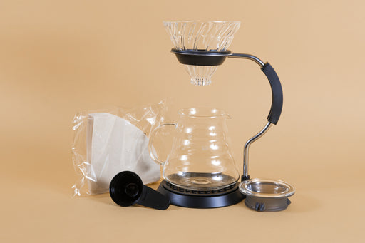 All glass cone shaped coffee dripper over an all glass coffee server with handle in a metal and rubberized plastic arm stand with a pack of filters, black plastic scoop, and server lid.