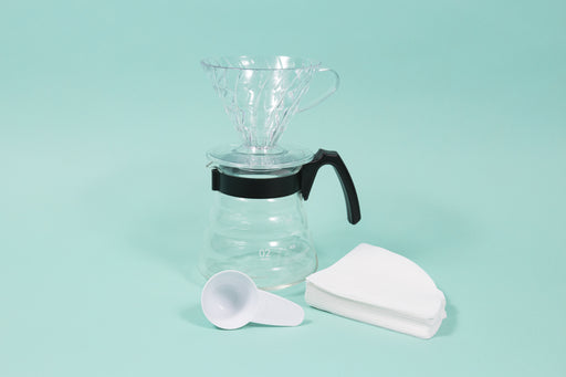 Clear plastic conical coffee dripper atop a glass coffee server i black plastic handle next a stack of filter and white plastic scoop