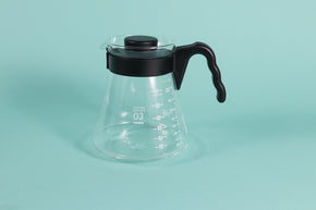 Glass coffee server with white text and level markings with black hard plastic handle and lid on a teal backdrop