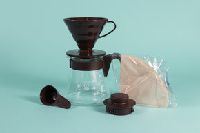 Chocolate brown cone shaped plastic dripper sitting on a glass server with brown plastic handle next to a pack of brown filters and brown plastic lid and scoop