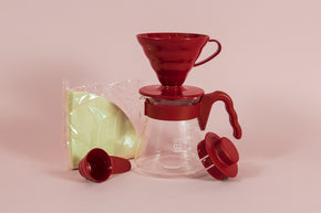 red all plastic cone shaped dripper sitting on a glass server with red plastic handle next to a pack of brown filters and red plastic scoop and lid.