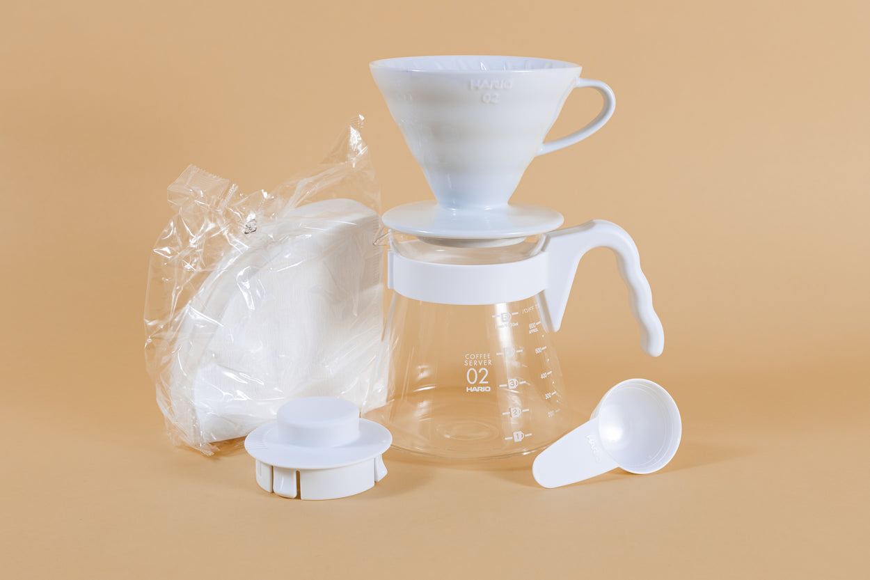 White cone shaped ceramic dripper with handle sitting on a glass server with white plastic handle next to pack of white cone filters white plastic lid and scoop.
