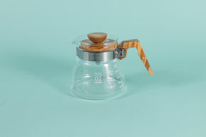 Glass coffee server with white text and markings with a brushed metal collar and wooden handle and lid on a teal backdrop