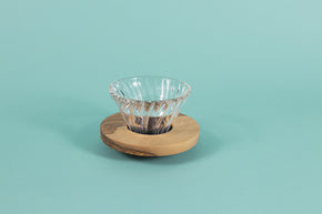 Clear all glass cone shaped coffee dripper with ribs, sitting in a round olive wood base.