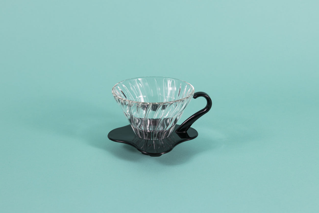 Clear all glass cone shaped coffee dripper with ribs, sitting in a black plastic base and handle.