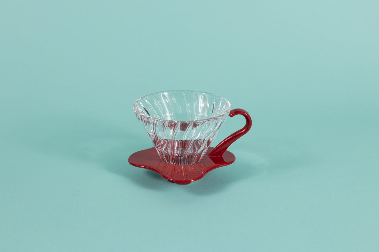 Clear all glass cone shaped coffee dripper with ribs, sitting in a red plastic base and handle.