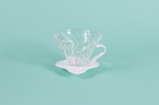 Clear all glass cone shaped coffee dripper with ribs, sitting in a white plastic base and handle.