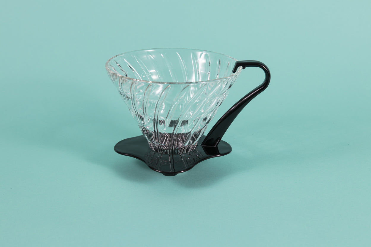 Large clear all glass cone shaped coffee dripper with ribs, sitting in a black plastic base and handle.