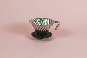 Silver metal cone shaped dripper with ribs and metal handle with a round black rubber base on a pink backdrop