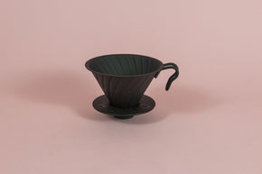 Matte black metal cone shaped dripper with ribs and metal handle with a round black rubber base on a pink backdrop