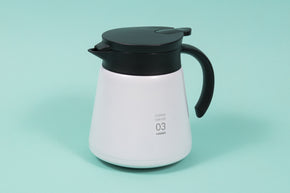 White metal coffee server with black plastic handle and lid with pour spout on a teal backdrop.