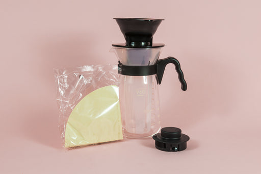 Tall glass coffee decanter with black plastic handle with a frosted plastic insert and black plastic cone dripper on top with black plastic server lid and pack of brown filter