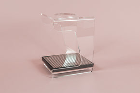 Clear acrylic stand with hole for cone dripper and black plastic drip with chrome screen on a pink backdrop